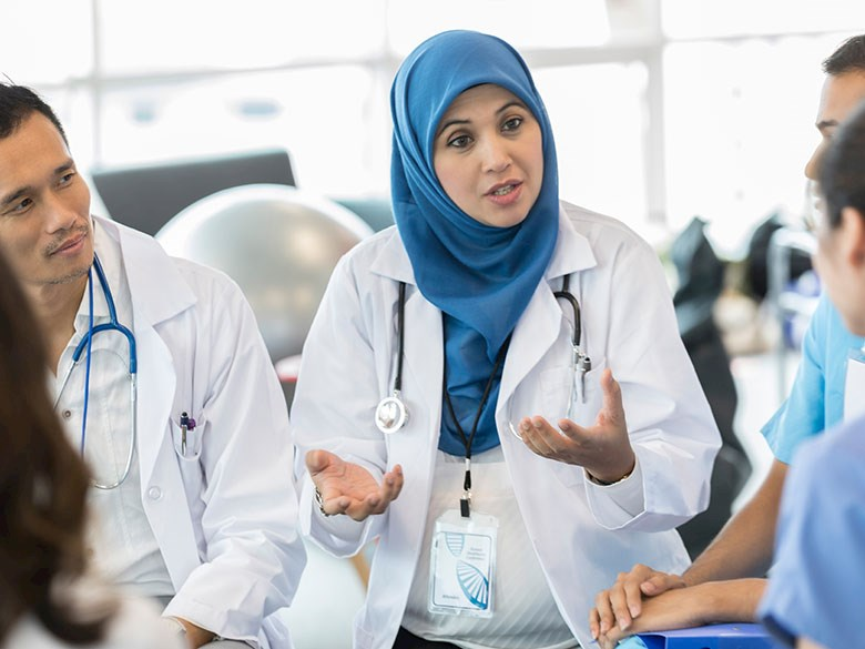 Doctor wearing a hijab in discussion with colleagues.