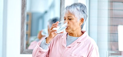 An older woman swallows pills with a glass of water.
